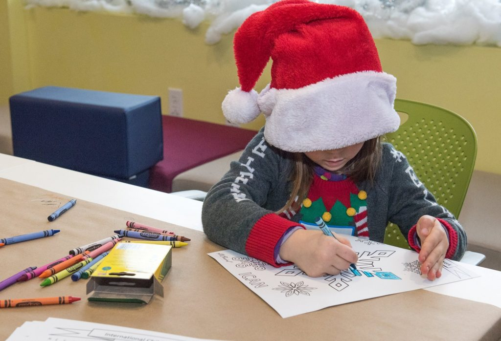 Child with over sized Santa Hat colors with crayons