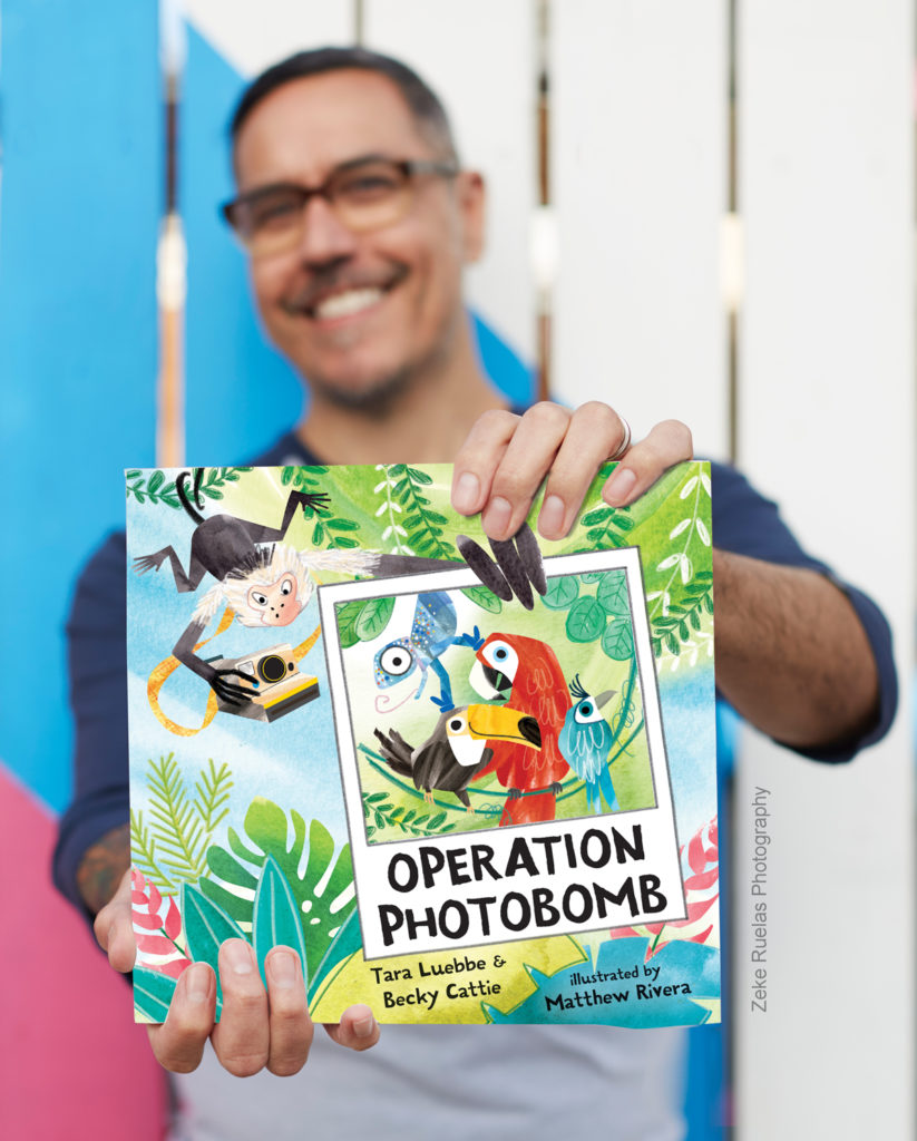 Illustrator Matthew Rivera holds book Operation Photobomb; the cover features toucan, parrot, cotinga and chameleon in a photograph being held by the character monkey