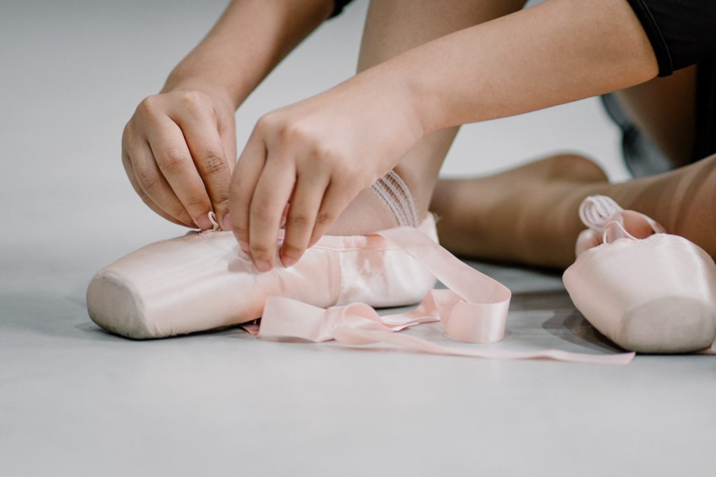 Child's hands lacing up pink ballet slippers