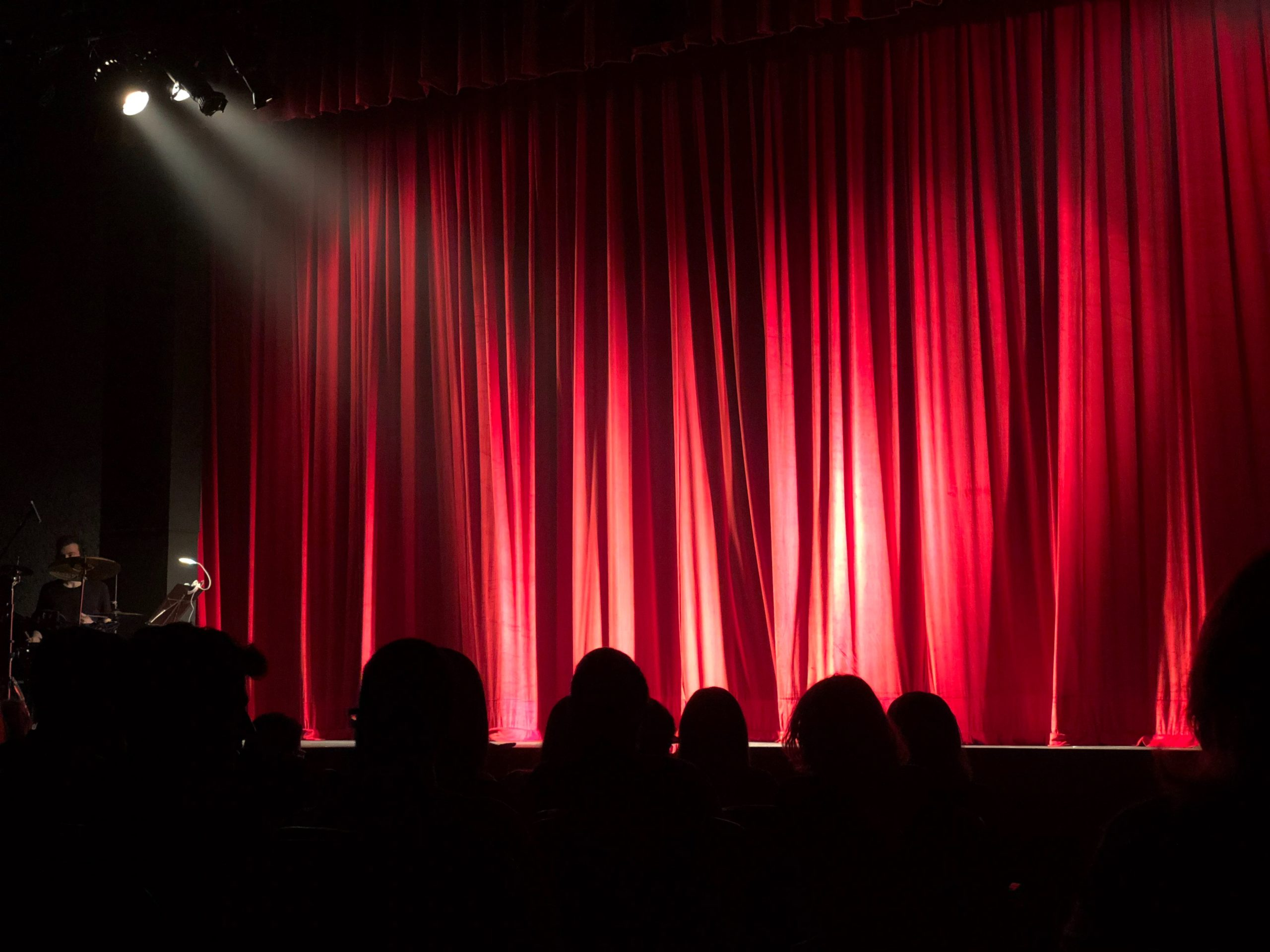 A red curtain down on a stage, silhouettes of audience members.